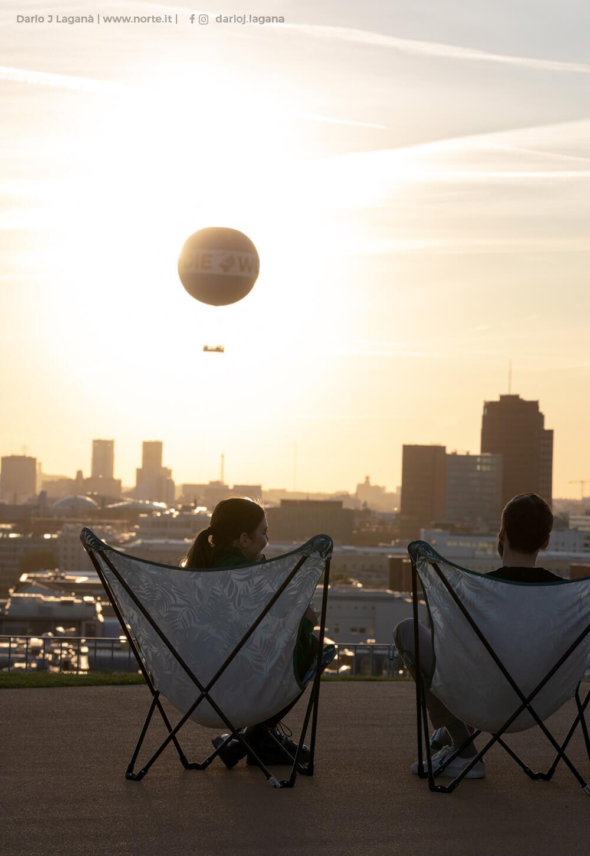Zwei Menschen in Sonnenstühlen blicken über Berlin mit WELT-Heißluftballon am Himmel