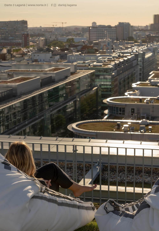 Frau im Sitzsack blickt über das Geländer der REM auf die Dächer Berlins