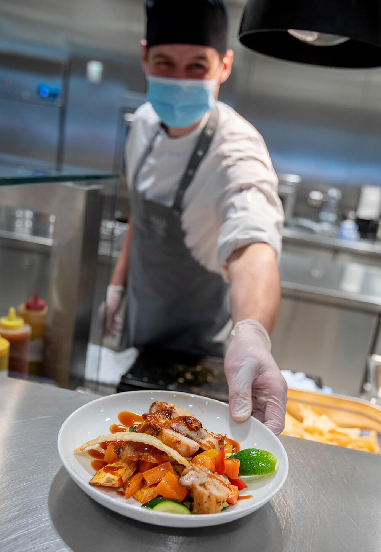 Koch reicht Gericht über den Tresen in der CANTEEN